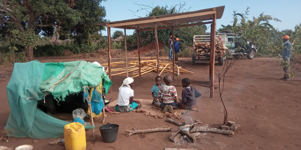 Gogo and her orphans watch their new house being built.